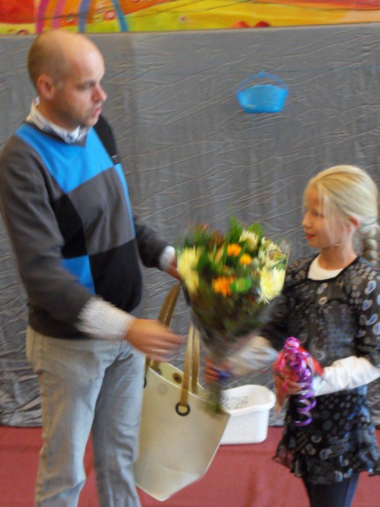 De 4000ste bezoekster krijgt bloemen van voorzitter Henk Tissing